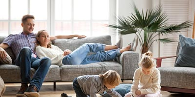Thirty-something couple on couch watching two kids play and wondering if they should be shopping for life insurance.