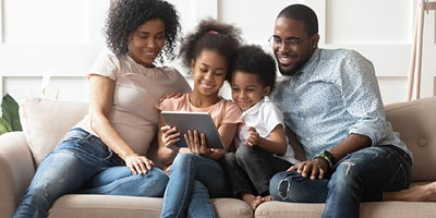 Family on a couch in their living room looking at a tablet to research life insurance companies.