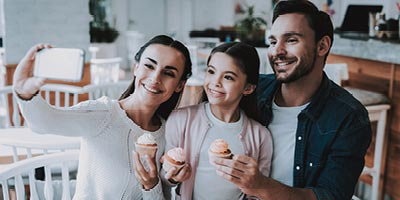 Smiling mom holds out her phone to take a photo of herself with husband and young daughter posing with pretty cupcakes at a bakery