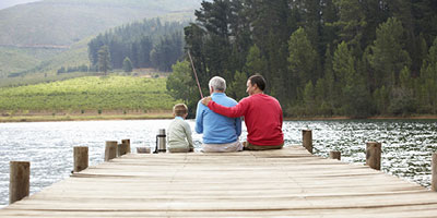 Senior man with fishing rod sits in between his son and young grandson on dock overlooking lake