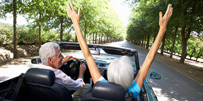 Senior couple driving in a convertible with the top down on a sunny day