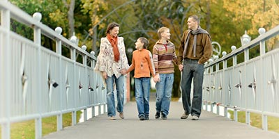 Family walking together on bridge.