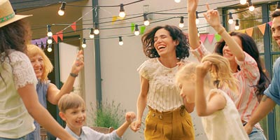 Multigenerational family dancing together at a backyard party