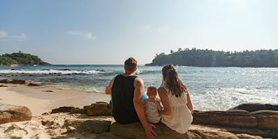Young family sitting on the beach and looking out over the ocean.