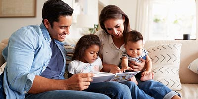 A young family sits on the couch together and reads a book.