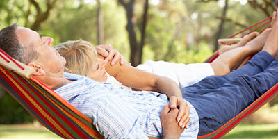 Senior aged couple laying in a hammock together.