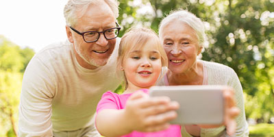 Grandparents using a smartphone with their granddaughter.