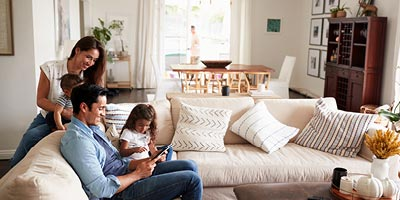 Young family sitting in their home that is protected with mortgage insurance.