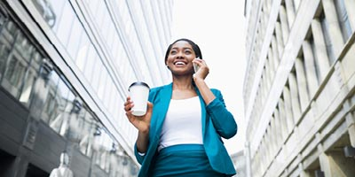 Young businesswoman talking on the phone with a Protective Life insurance agent discussing her life insurance options.