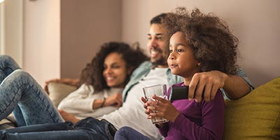 Young family sitting together in their home resting assured that they have ample life insurance coverage for their needs.