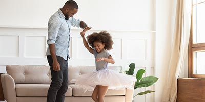 Father and daughter dancing at home, thankful that the father bought child life insurance.