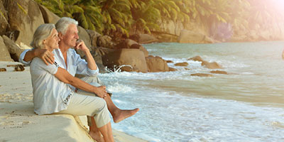 Couple sitting together on the beach as they discuss whether or not they need to use their accelerated death benefits.