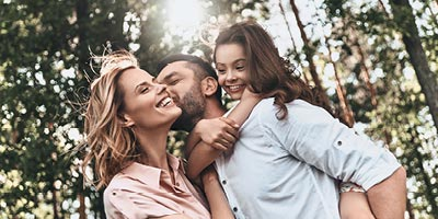 Young couple with a small child hugging and feeling happy that they have life insurance.