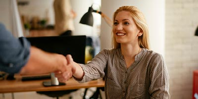 Woman shaking hands with a financial advisor to put her life insurance policy into place.
