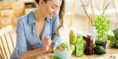 A woman eating a salad to benefit her heath and affect her life insurance rates for the better.