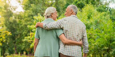 Older couple walking with arms around each other after planning for burial insurance and funeral costs.