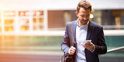 Young man walking in a city setting and browsing his smartphone.