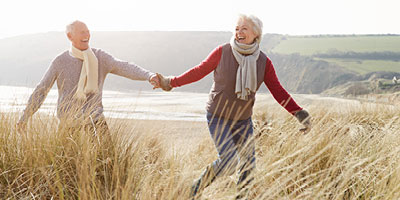 A senior adult couple holding hands as they walk across a beach in the winter.