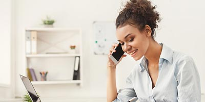 Young woman talking on the phone while she works on how she can trim her life insurance budget.
