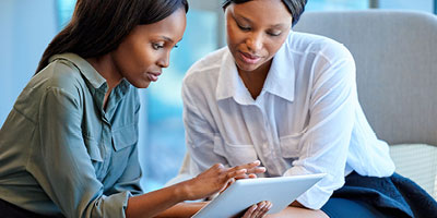Two African-American women discussing who to name as their life insurance beneficiary.