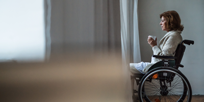 Woman sitting in a wheelchair looking out the window while drinking coffee.