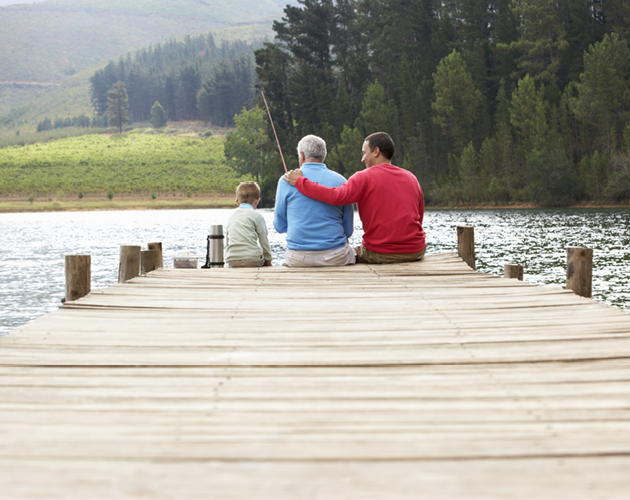 Father, adult son and young grandson fishing from pier on a lake.