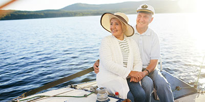 A senior adult couple sailing on the ocean.