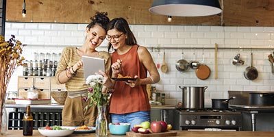 Two females looking and smiling while looking at their tablet computer and eating.
