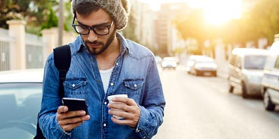 Young man walking, drinking coffee, and exploring credit insurance options on his smartphone.
