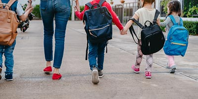 image of female adult walking and holding hands with young children who look like students.
