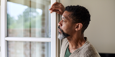 African-American man gazes out the window of his home.