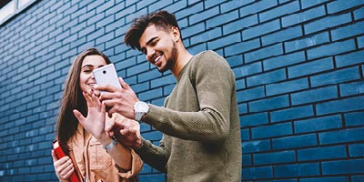 A man smiling and showing his female friend his phone.
