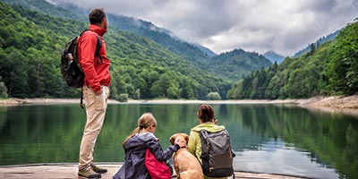 Active family on the bank of a lake looking at the view.