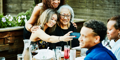 Grandmother, mother, and daughter posing for a three generation selfie.