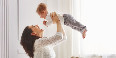 Young mom lifting her baby above her head and joyously flying him through the air.