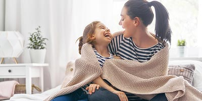 Mother and daughter laughing; mother is worried if she can get life insurance on her ex