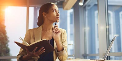 African-american woman looking off with pen, trying to determine how to determine how much life insurance she will need