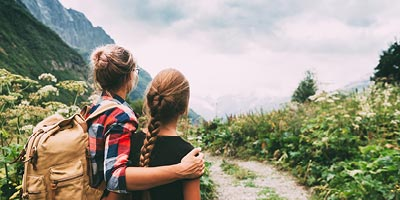 Mom with arm around teenage daughter as they look at a mountain in the distance from hiking trail