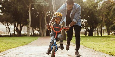 Father teaching his young son to ride a bike.