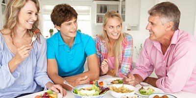 Family with grown children eating healthy lunch at their kitchen table.