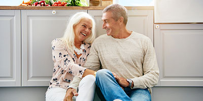 Older couple laughing in kitchen.