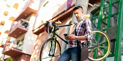 Man looking at his phone while holding his bike in a downtown area.