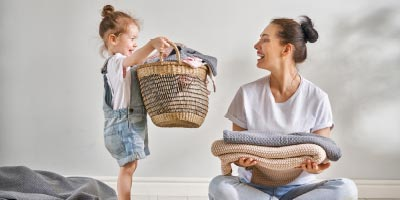 Young Mother and her young child working together to fold laundry.