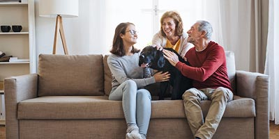 Parents with their only daughter and pet dog in a comfortable family setting.
