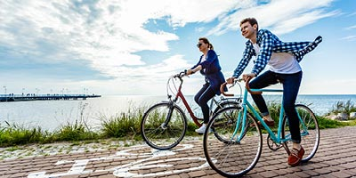A young couple biking along the ocean with the benefit of having permanent life insurance.