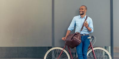 Man smiling outside while holding his phone and leaning against his bicycle and a wall.