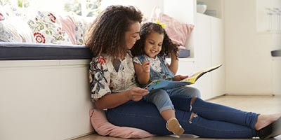 Young mother and daughter smiling while reading a book.