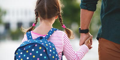 Father and daughter with backpack walking to school