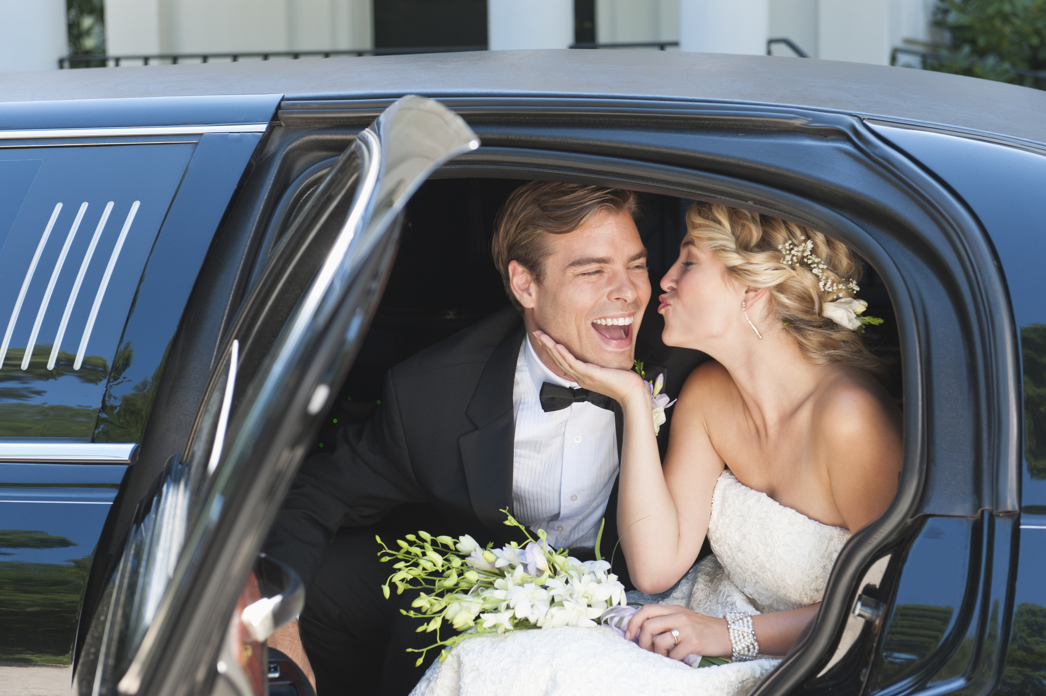 A couple getting into a limousine and leaving their wedding.