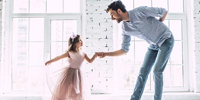 Dad bowing to his young daughter who is dressed in a ballet tutu and ready to dance.